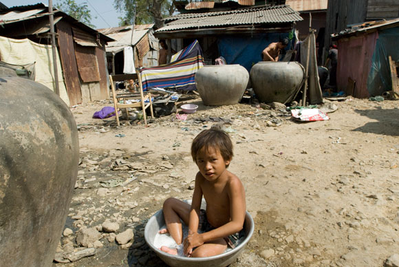 boy bathing in community on edge of slum